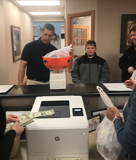 Dentist and child weighing candy donation for troops