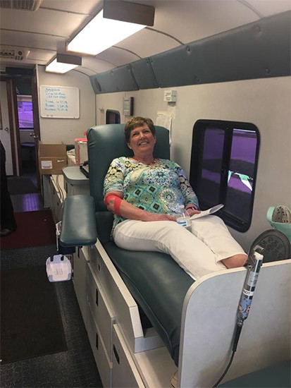Smiling dental team member giving blood