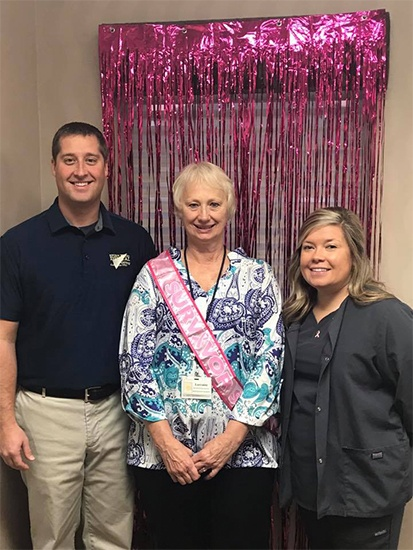 Two dental team members smiling with patient wearing a pink sash
