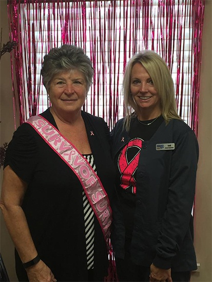 Smiling patient wearing a pink sash posing with dental team member