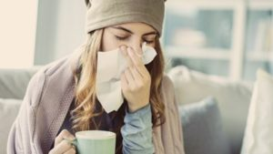 Woman holding a mug in one hand and holding a tissue to her nose with the other